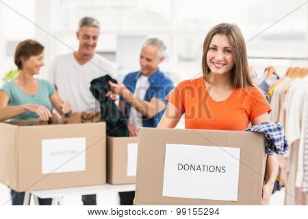 Portrait of smiling casual businesswoman holding donation box in the office