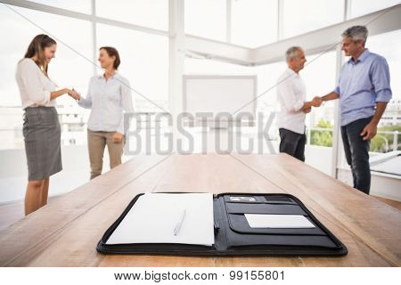 Planner in front of handshaking business people in the office