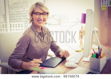 Portrait of smiling casual designer working at her desk in the office