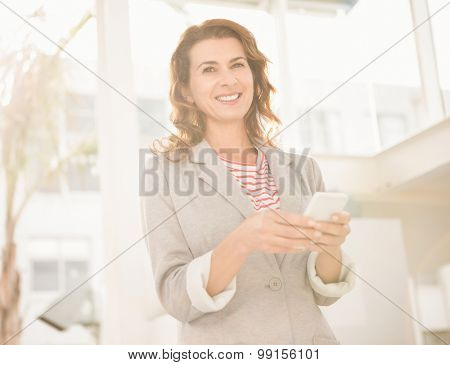 Portrait of smiling casual businesswoman holding smartphone in the office