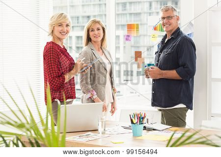 Portrait of standing business team holding a tablet at office