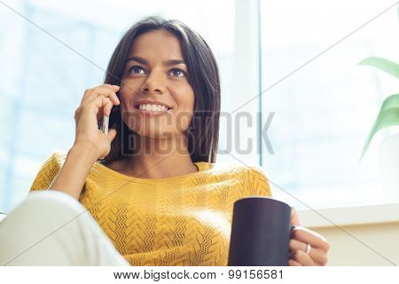 Portrait of a happy thoughtful businesswoman talking on the phone and holding cup with coffee in office. Looking away