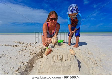 mother and son building sand castle on tropical beach
