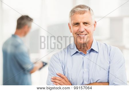 Portrait of a smiling businessman with arms folded at the office