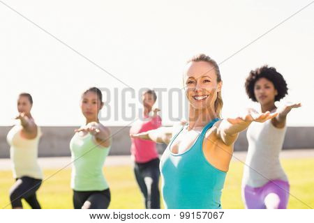 Portrait of smiling sporty blonde doing yoga in yoga class in parkland