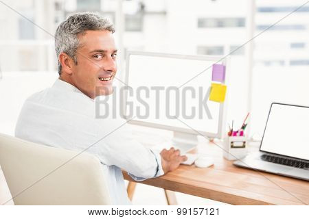 Portrait of smiling casual businessman working with computer in the office