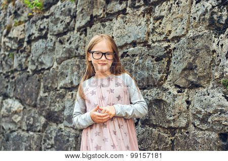 Outdoor portrait of a cute little girl in a city, wearing eyeglasses and dress