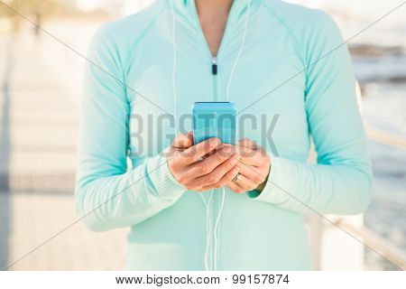 Fit woman listening to music and holding phone at promenade
