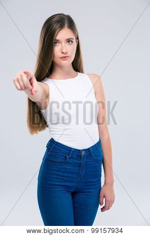 Portrait of a serious female teenager pointing finger at camera isolated on a white background