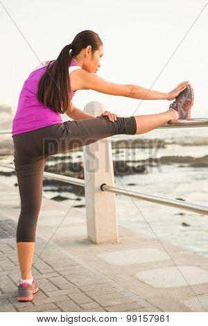 Fit woman stretching leg on railing at promenade