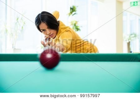 Charming woman playing billiards indoors