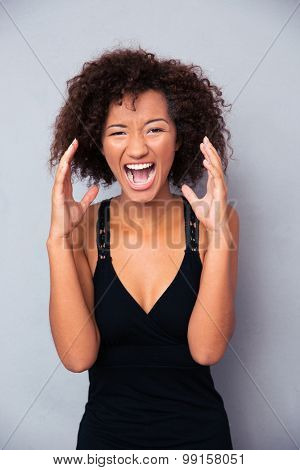 Portrait of african woman shouting over gray background