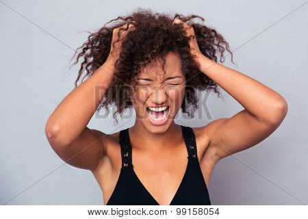 Portrait of afro american woman shouting over gray background