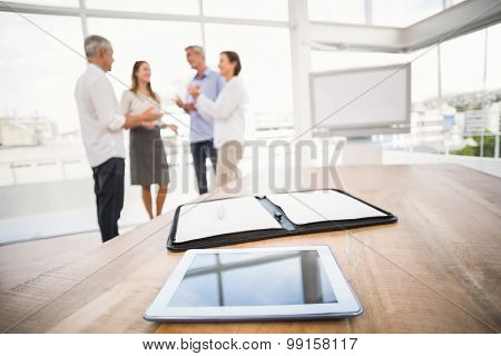 Tablet and planner in front of talking business people in the office
