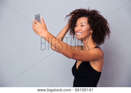 Portrait of a smiling afro american woman making selfie photo on smartphone over gray background