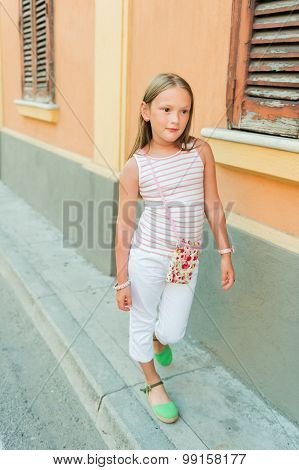 Outdoor portrait of a cute fashion little girl wearing white trousers and green shoes