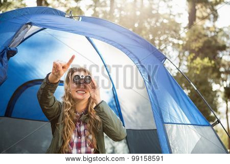 Smiling blonde camper looking through binoculars while sitting in tent