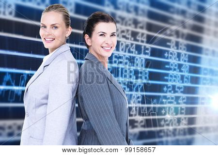 Attractive businesswomen standing back-to-back against stocks and shares