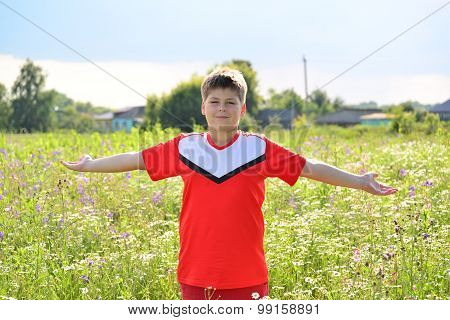 Teenage Boy Stands In Meadow Arms Outstretched To The Sides