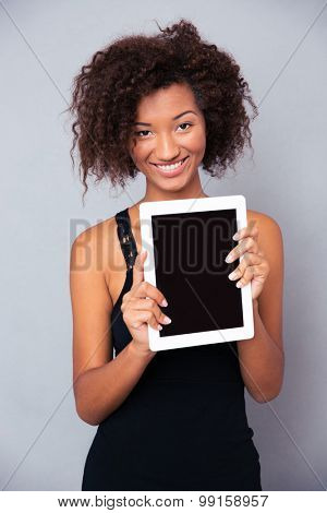Portrait of a happy afro american woman showing blank tablet computer screen isolated on a white background