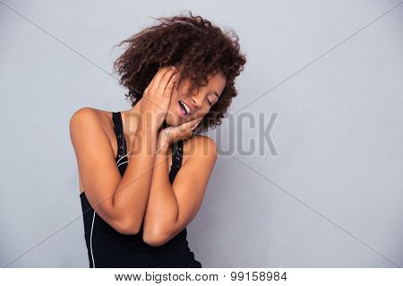 Portrait of a cheerful afro american woman listening music in headphones over gray background