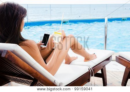 Portrait of a young woman lying on deckchair with smartphone and cocktail outdoors