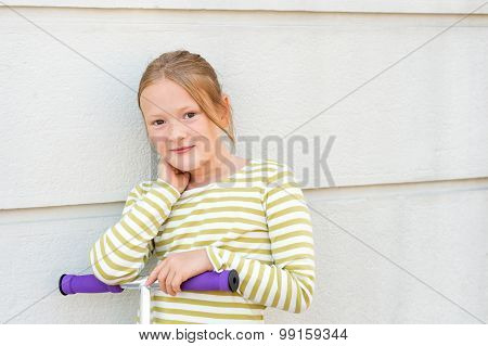 Close up portrait of adorable young 8 years old girl leaning on hir scooter