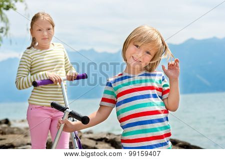 Two cute kids playing by the lake, holding their scooters