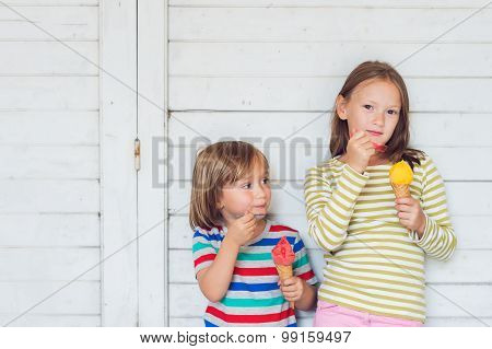 Portrait of two adorable kids eating colorful ice cream