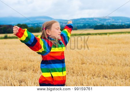 Adorable little girl playing in a field, arms open wide, wearing rainbow rain coat