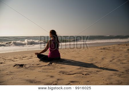Woman doing yoga on beach.