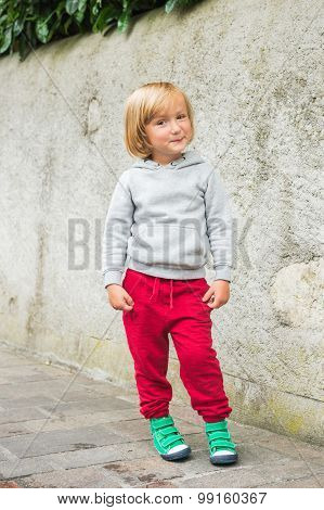Fashion portrait of adorable toddler boy wearing grey sweatshirt, red trainings and green shoes