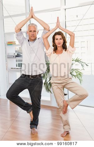 Portrait of peaceful casual business colleagues doing yoga in the office