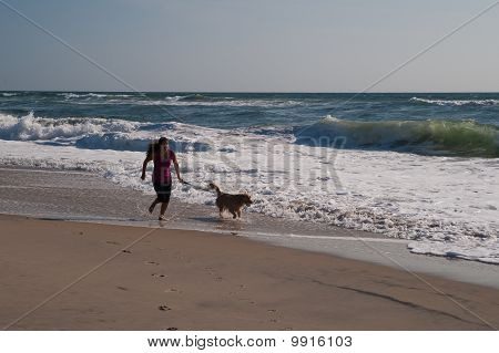 Girl and dog running on beach