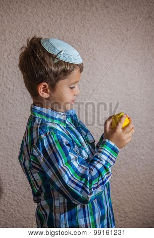 Citrus -  ritual fruit for the Jewish holiday of Sukkot. Beautiful seven year old boy in white knitted skullcap is holding citrus