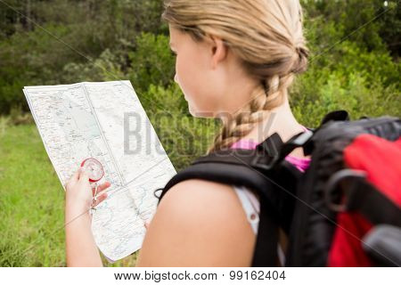 Blonde hiker with compass and reading map in the nature