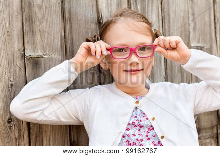 Close up portrait of a cute little girl of 7 years old, wearing pink eyeglasses