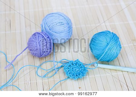 Colorful clews and crochet hook on wooden background