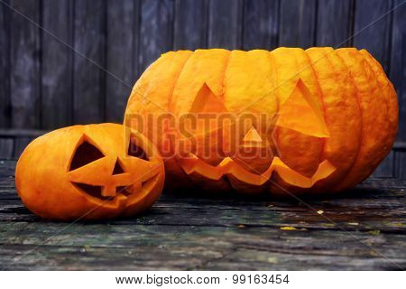 Two Jack-o'-lantern On An Old Wooden Table.