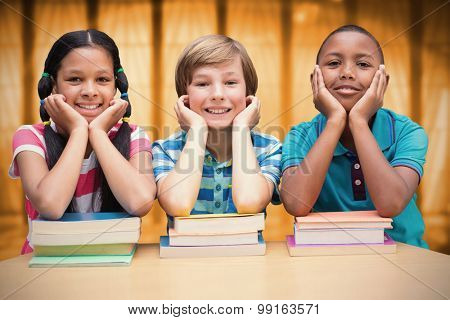 Cute pupils looking at camera in library against window overlooking city