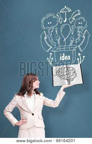 Pretty businesswoman showing a book against blue background