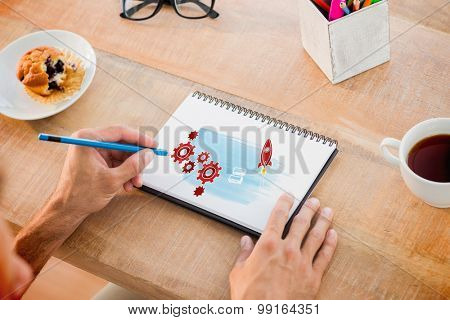 Man writing notes on notebook against rocket and cogs graphic