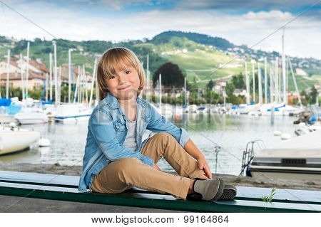 Fashion portrait of a cute little blond boy sitting on a bench by the lake