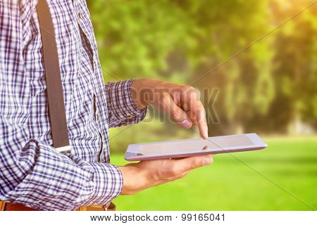 Geeky businessman using his tablet pc against trees and meadow