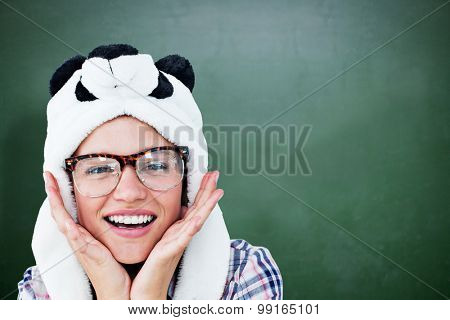 Geeky hipster smiling at camera against green chalkboard