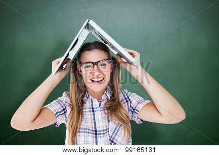 Geeky hipster holding her laptop over her head against green chalkboard