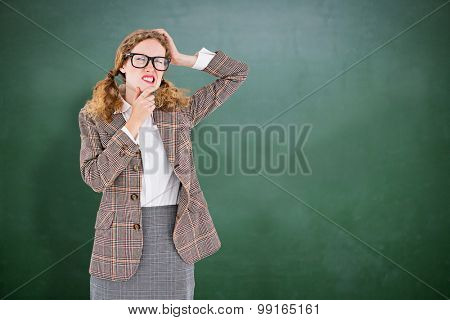 Geeky hipster thinking with hands on chin and temple against green chalkboard