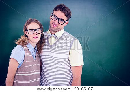 Happy geeky hipster couple with silly faces against green chalkboard