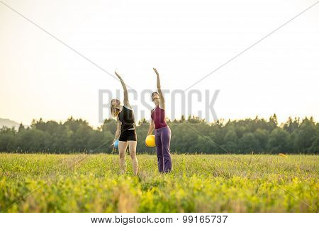 Two Young Fit Women Doing Pilates Exercise Lifting One Arm In The Air