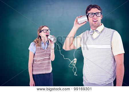 Geeky hipster couple speaking with tin can phone against green chalkboard